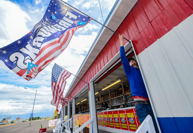Alex Vance, manager at 3 Local Guys fireworks stand, adjusts the flags flying outside of the stand located on the east end of 10th Avenue South, Wednesday.