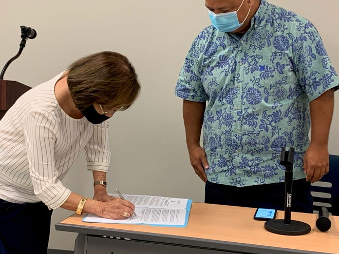 Guam Education Board Chairwoman Maria Gutierrez, left, signs a resolution at Tiyan, adopting the school system's reopening plan, as education Superintendent Jon Fernandez looks on in this file photo.
