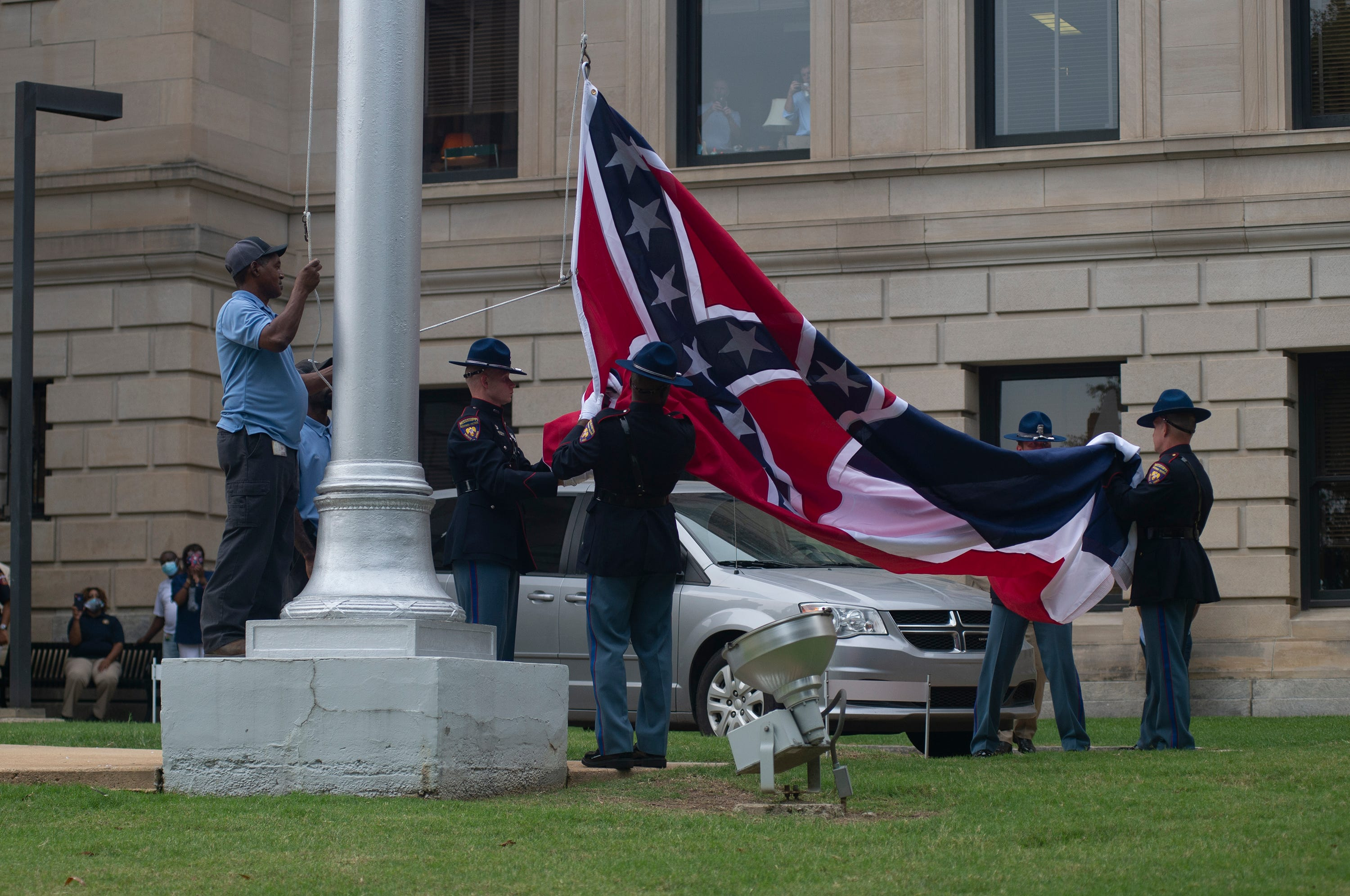 The Mississippi state flag is lowered for the last time and folded by the Mississippi Highway Patrol Honor Guard during a flag retirement ceremony at the state Capitol in Jackson on July 1, 2020. After the ceremony, the flag was presented to the Mississippi Museum of History.