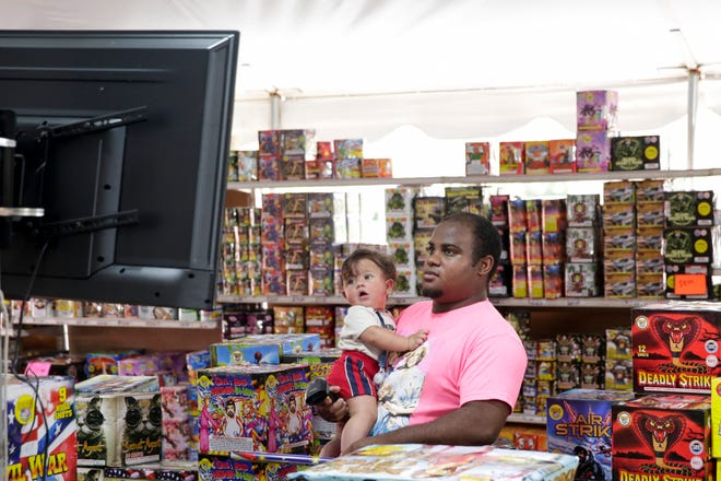 Marques Rayford and his son, Carter, six-months-old, watch a screen showing different firework explosions at Scott's Tent of Snakes and Sparklers, Wednesday, July 1, 2020, in Lafayette.