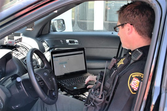 Dep. Brandon Brown of the Marion County Sheriff's Office checks his email for a daily training memo. All deputies can access training resources on the laptop computers in their cruisers, Chief Deputy Aaron Corwin said.