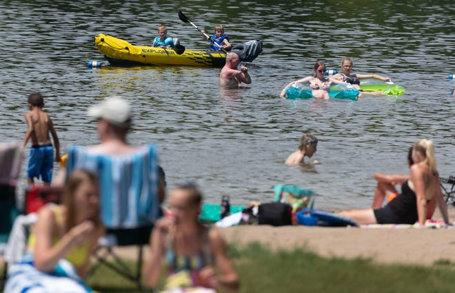 People cool off in the water at Hartman Creek State Park in Waupaca in July. Citing the important of tourism for the state economy, Gov. Evers has launched an $8 million grant program for tourism promotion and development groups hurt by the COVID-19 pandemic.