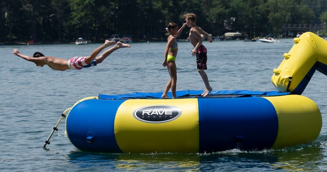 KIds frolic on a floating trampoline on Round Lake in Waupaca. The Chain O'Lakes - a string of 22 lakes in Waupaca County - have been a popular vacation destination for families for decades.