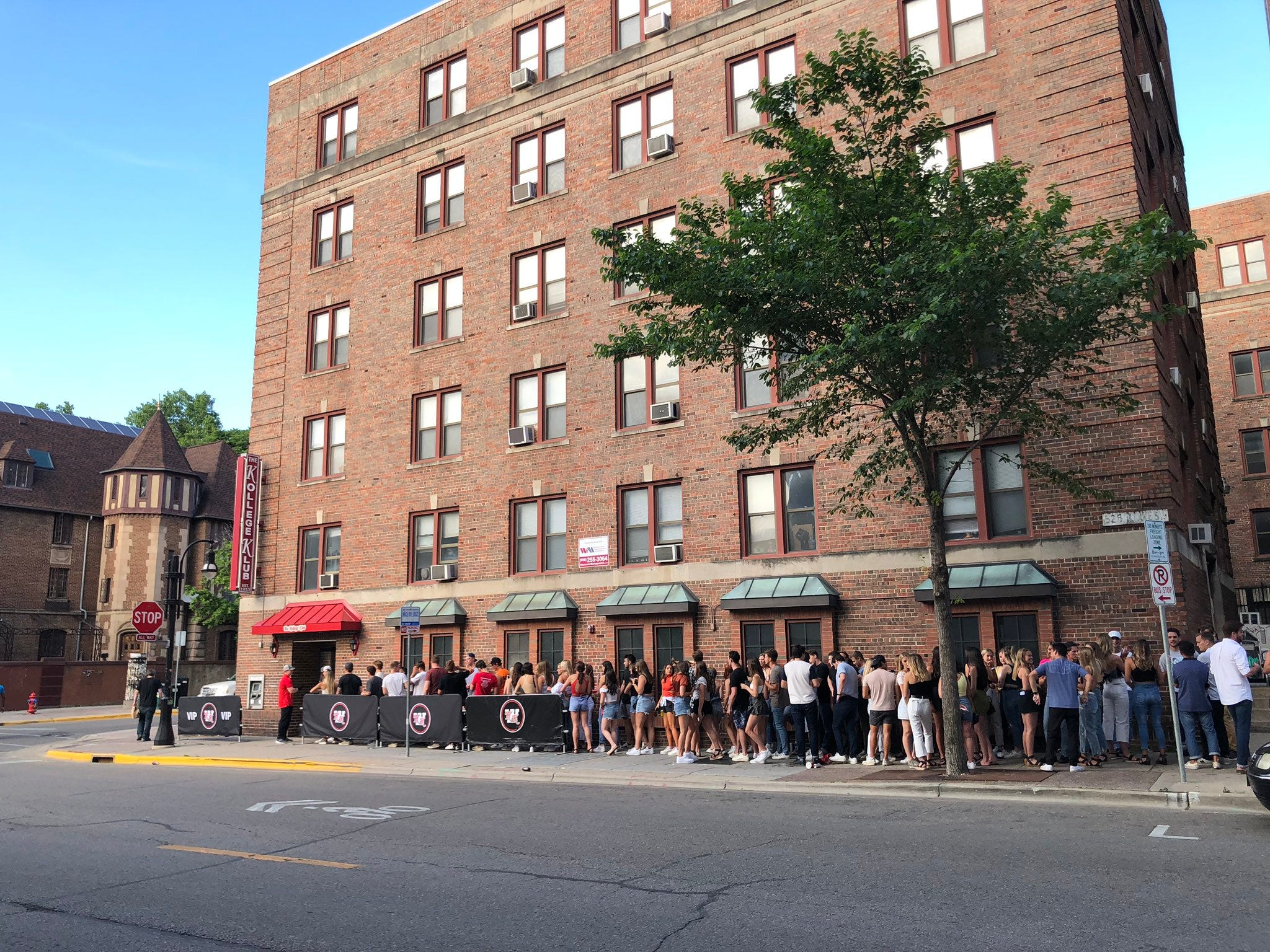 Young Madison residents line up outside of the Kollege Klub bar near UW-Madison's campus on June 18.