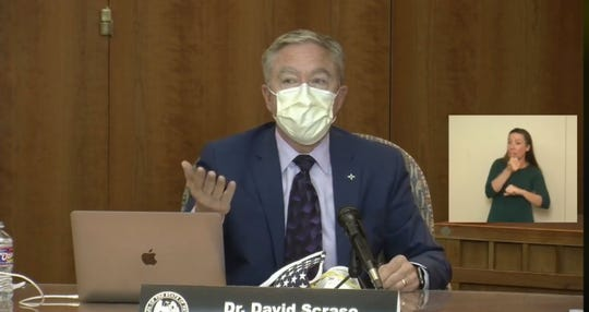 New Mexico Human Services Secretary David Scrase demonstrates proper mask-wearing during a virtual news conference from the state Capitol building in Santa Fe on Wednesday, July 1, 2020.