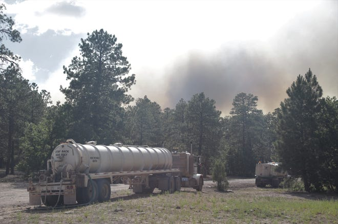 Smoke from the Wood Springs Two Fire rises in the background on June 29 as trucks sit parked along Navajo Route 7 in the Fluted Rock area near Sawmill, Arizona.