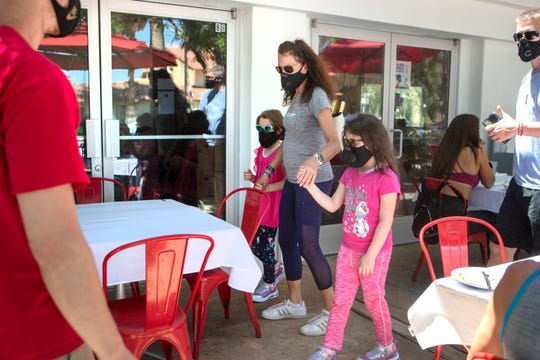 Kimberly McDermott, center, walks to be seated with her nieces Makena, left, and Naomi Wilcox at Chicken Ranch in Palm Springs, Calif., on Wednesday, July 1, 2020. Governor Newsom restricted several counties, including Riverside County, to outdoor seating only for restaurants after an increase in coronavirus cases statewide.