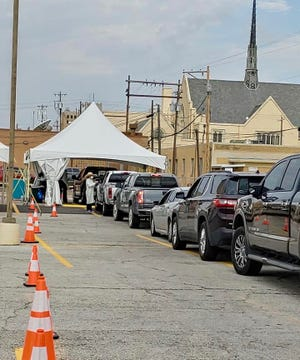 A line of cars approaches the mobile Shannon Medical Center COVID-19 testing site at 110 E. Twohig St.