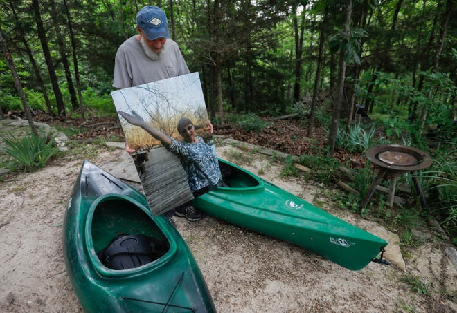 Kirk Farrell looks down at a photo of his wife Rita Farrell who died in a kayaking accident on Bull Creek. Her kayak is on the right; both kayaks were found two miles downstream after the tragic incident.