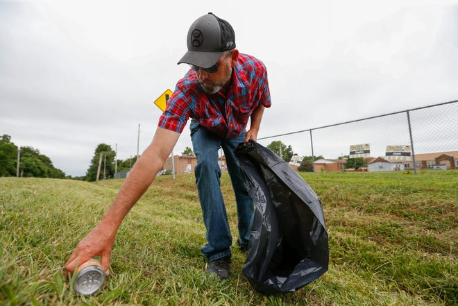 Michael Wallace, superintendent of the Everton school district, picks up trash outside the school along a road Wednesday. He is mowing the campus to save money amid budget cuts.