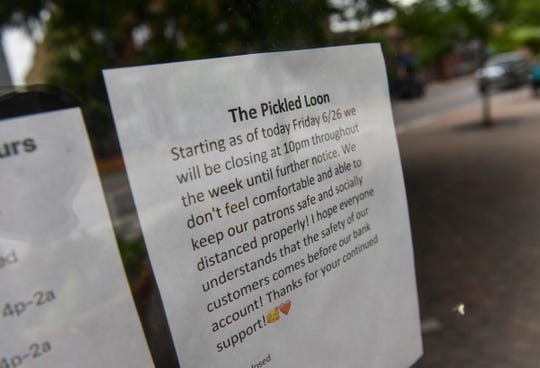 A sign is posted to a front window of The Pickled Loon Wednesday, July 1, 2020, in downtown St. Cloud.