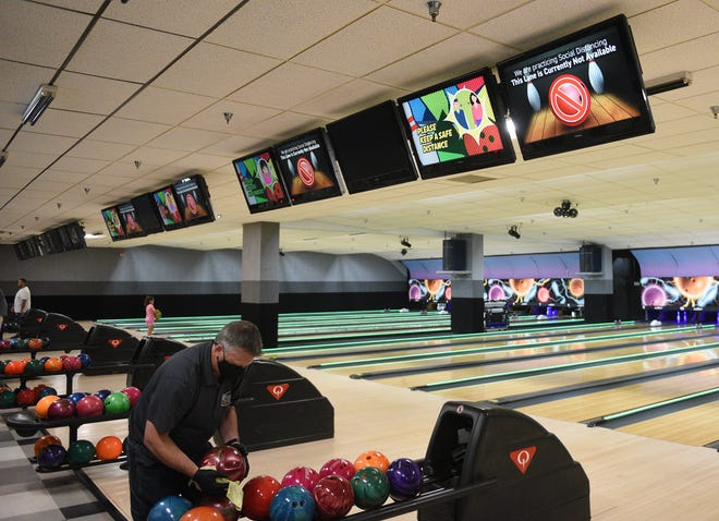 Rod Neuenschwander, head of bowling operations at Great River Bowl, sanitizes bowling balls Tuesday, June 30, 2020, in Sartell.