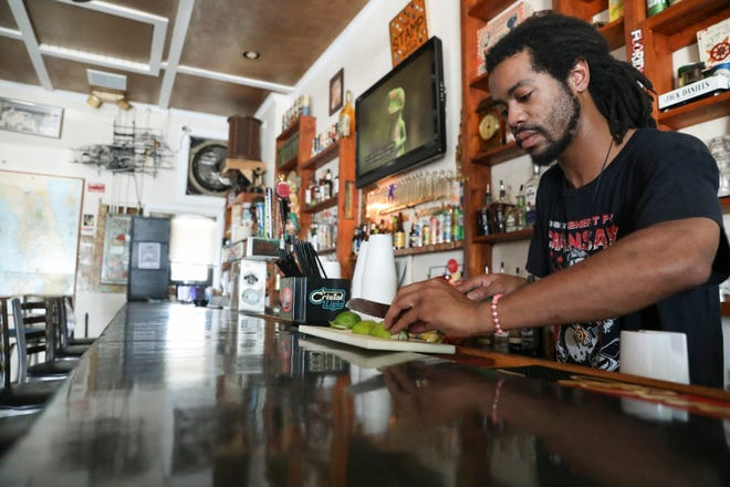 """I've had three customers,"" says bartender Anthony Robertson as he cuts oranges at The Stamp Bar on June 30, 2020, in Vero Beach. Jared Smith (not pictured), owner of The Stamp Bar and The Boiler, is having to resort to take-out and delivery-only alcohol sales due to the coronavirus pandemic."