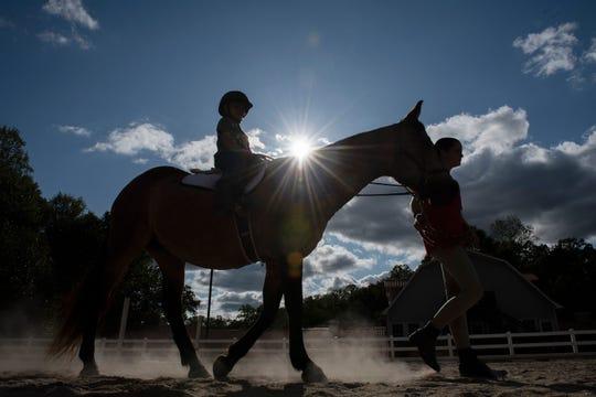 Meghan O'Hare walks a horse as Deklan Corrigan rides during a lesson at Eden Farms.