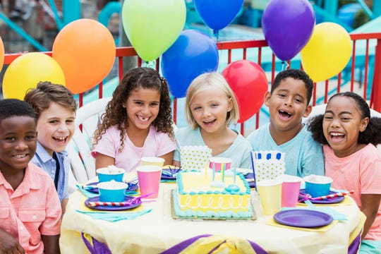 A group of children sit together around a birthday cake.