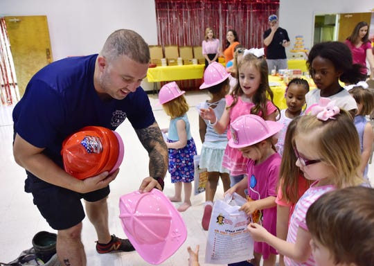 Travis Holt, owner of Big Red Party Truck, hands out plastic fire fighter helmets during a birthday party.