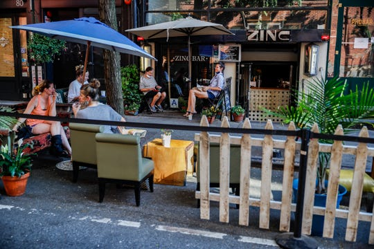 Customers dine outside PhoBar, Monday, June 22, 2020, in New York. New York City Mayor Bill de Blasio says he is delaying the planned resumption of indoor dining at restaurants in the city out of fear it would ignite a a spike in coronavirus infections.
