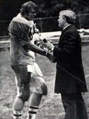 Former West Liberty football player Randy Little, from Tri-Valley, is congratulated by school president Dr. David Chapman after a game in 1974. Little, a member of the school's Hall of Fame, died on Friday at 67.