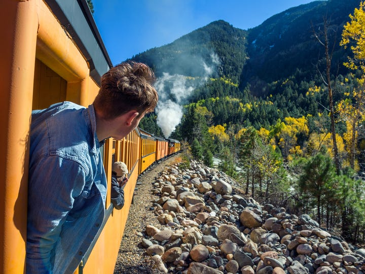 Young man looking out of train window on the historic steam engine train travelling from Durango to Silverton along the Animas River in Colorado.