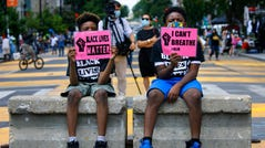 """In this June 24, 2020, file photo, Tyshawn, 9, left, and his brother Tyler, 11, right, of Baltimore, hold signs saying """"Black Lives Matter"""" and """"I Can't Breathe"""" as they sit on a concrete barrier near a police line as demonstrators protest along a section of 16th Street that has been renamed Black Lives Matter Plaza in Washington. Thousands of Black activists from across the U.S. will hold the 2020 Black National Convention on Aug. 28, 2020, via livestream to produce a new political agenda that builds on the protests that followed George Floyd's death."""