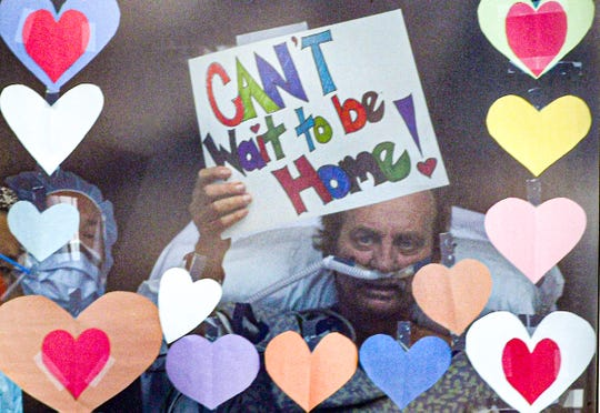 """Richard Frady, a recovering COVID-19 patient in the intensive care unit at AnMed Health in Anderson, S.C., waves a """"Can't Wait to be Home!"""" sign on his 32nd day after diagnosis to his wife, Sally, and daughter Allison Nissen from his window at the hospital April 28."""