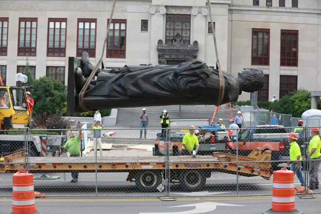 Workers place the Christopher Columbus statue onto a flatbed truck after removing it from its pedestal in front of Columbus City Hall on Wednesday morning, July 1, 2020.