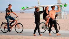 Surfers carry their boards as cyclists ride past, none wearing a face mask, at Santa Monica Beach near Santa Monica Pier, which re-opened with safety guidelines June 25.