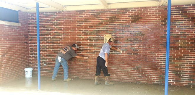Workers fro m Ardmore Parks and Recreation scrub graffiti from the wall at the Ardmore Community Water Park Thursday morning.