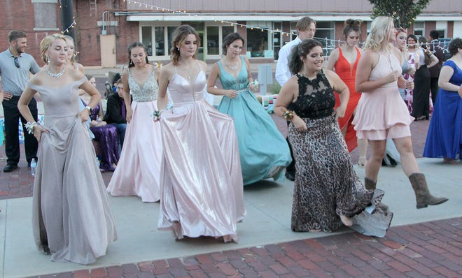 Dancers lift their skirts to prevent tripping as they do a line dance to Copperhead Road during Skyline High School's 2020 outdoor prom. Though their theme was 'A Night in the Country' students enjoyed hanging out, visiting and dancing at Pratt's Merchants Park for the rescheduled outdoor event.