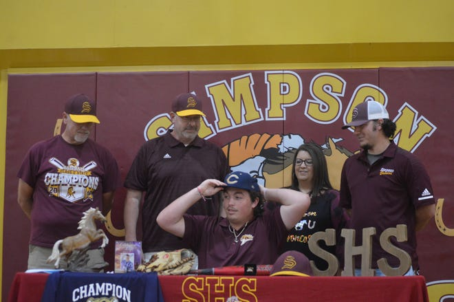 Simpson senior Landon Meyers dons a Champion Christian cap after signing with the school Wednesday.