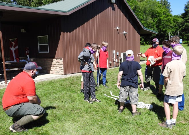 Dominic Lehman, director of the Muskingum Valley Scout Reservation, watches Clark Schwenke instruct campers from Bremen on first aid techniques. Usually another scout is used, but a plastic skeleton is substituting this year to minimize contact.