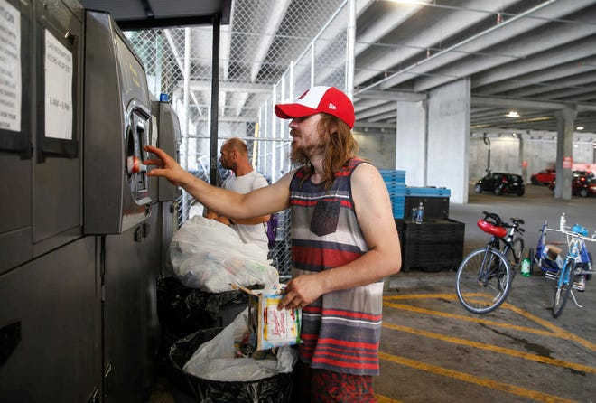 James Sturm of Des Moines places cans in the can redemption bin on Thursday, July 2, 2020, at the downtown Hy-Vee, one of only a handful of locations that still takes cans and bottles in Des Moines.