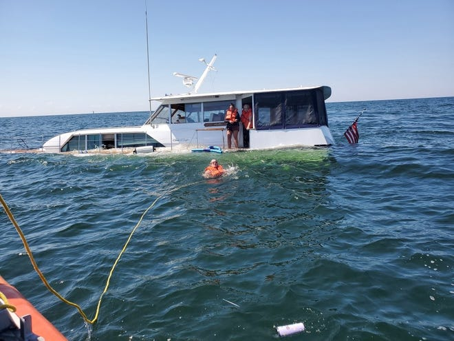 Five people and a dog were rescued from a sinking 50-foot boat in Saginaw Bay by a boat crew from Coast Guard Station Saginaw River Wednesday.
