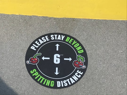 A sidewalk marker urges patrons to practice social distancing at Turtle Creek Stadium in Traverse City on July 2, 2020.