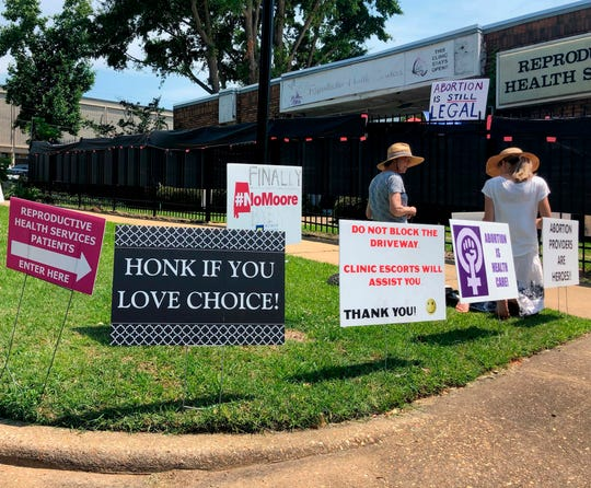 In this May 17, 2019, file photo, abortion opponents kneel in prayer outside Reproductive Health Services, an abortion clinic in Montgomery, Ala. The U.S. Supreme Court on Thursday, July 2, 2020, left intact a precedent that lets states and cities prevent people from approaching women without consent as they are entering a clinic.