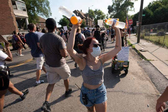 Volunteer Liv Puente hands out water to demonstrators as they march through southwest Detroit, July 1, 2020, to protest police brutality after a Detroit police vehicle drove through a crowd of protesters earlier in the week.