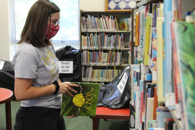 Alyssa Laurer, a library page at Birchard Public Library, reshelves books Wednesday. The library has reopened with precautions in place for visitors after being closed three months due to the pandemic.