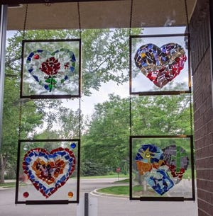 Mosaic hearts hang in a window at 3Hopeful Hearts on Whaler's Way in Fort Collins.