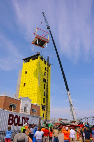 A crane lifts the Beacon Room to the top of the 10-story Maritime Lighthouse Tower under construction at the Door County Maritime Museum in Sturgeon Bay during a July 2 ceremony marking the occasion. The Boldt Co. is in charge of the project, and a May 1 opening is planned for the tower.