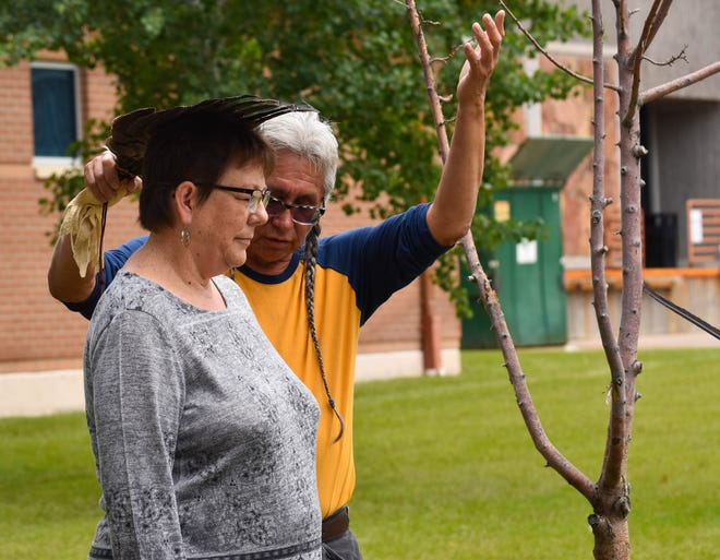 Michele Uhrich receives an Eagle Feather blessing from Great Falls MSU adjunct faculty member Don Fish for her academic achievements. Uhrich and fellow Great Falls College graduate Julius Scott have been named Montana All-American scholars.