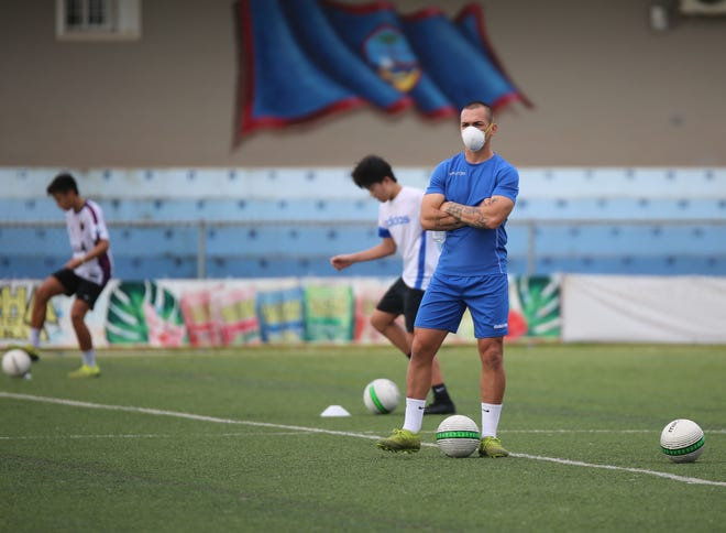 Jason Cunliffe, in blue, observes players during a U17 National Team training session Wednesday afternoon at the Guam Football Association National Training Center. Cunliffe, currently captain of the Matao, Guam Men's National Team, recently accepted an offer from Guam Football Association to become Guam's new U17 National Team Head Coach.
