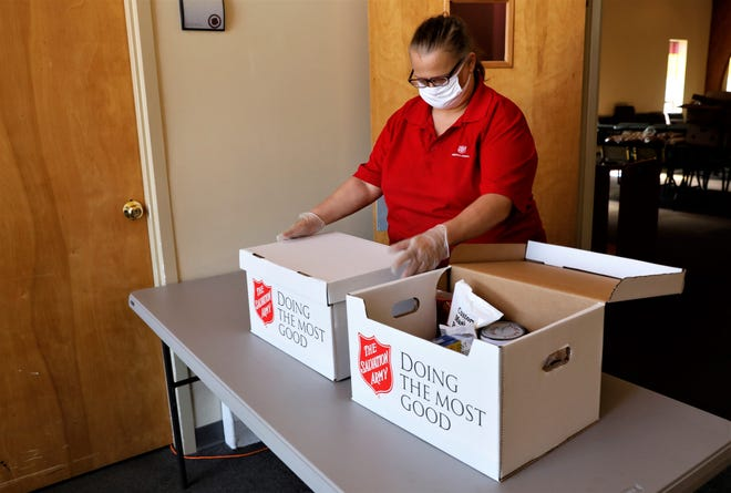Louella Thornton, a volunteer with the Salvation Army, examines the contents of meal boxes provided by the Federal Emergency Management Agency as part of a program providing relief to families in need during the coronavirus pandemic. The Salvation Army in Fairfield County distributed around 20,000 meals since March, nearly half of what they typically distribute for a whole year.