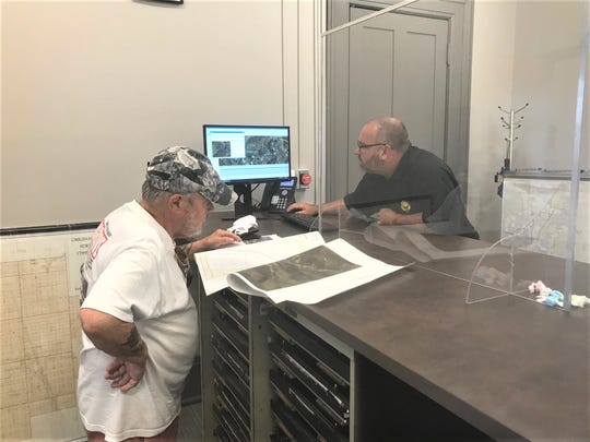 Graphic Information System Supervisor Andrew Boystel (left) helps a customer recently in the county's new real estate office at 108 N. High St.