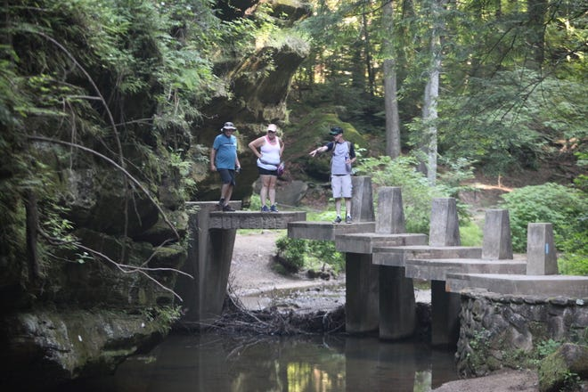 Hikers enjoy the newly reopened trail Thursday morning at Old Man's Cave in Hocking Hills State Park
