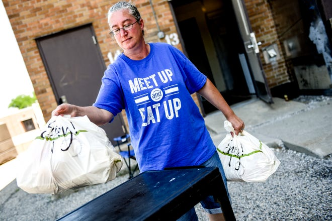Crystal Froum gets meals for families ready for pick up as part of the Lansing School District's Meet Up and Eat Up curbside food pickup on Thursday, July 2, 2020, at Sexton High School in Lansing.