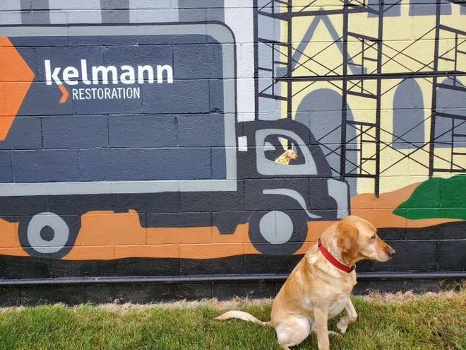 Mollie, a co-worker at Kelmann Restoration, in front of the mural on the back of the company's headquarters in Wauwatosa.