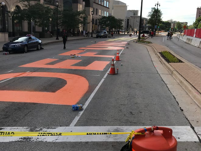 """Protesters on Wednesday closed Water Street in downtown Milwaukee and painted """"DEFUND THE POLICE"""" across the width of the street outside Milwaukee City Hall."""