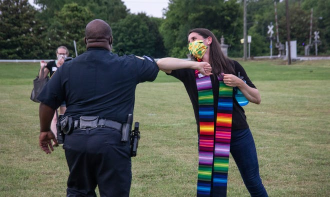 """The Rev. Sam McGlothlin, associate pastor of Belle Meade United Methodist Church, elbow bumps Sgt. Edward Rucker after """"A Prayer Service to Stand Against Racism"""" on June 5, 2020."""