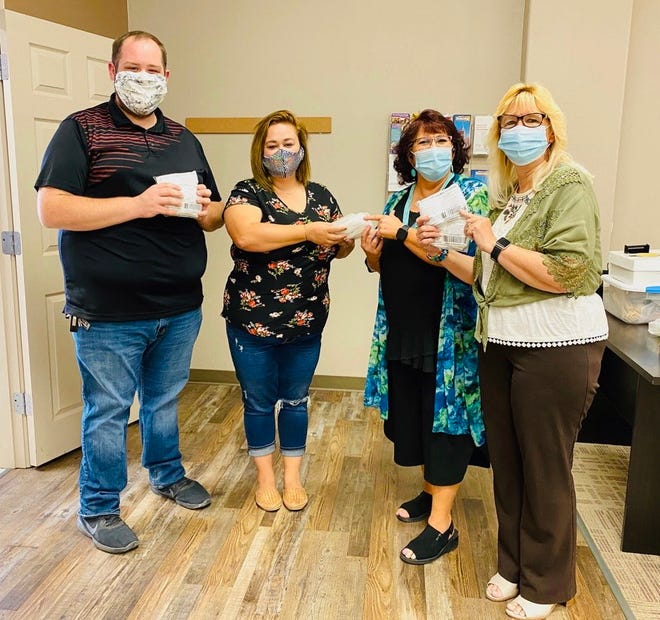 The Deming-Luna County Chamber of Commerce is distributing cloth face masks to local businesses. From left, Chamber Executive Director John Richmond and staffer Galen Gomez provide masks to Valerie Brea and Lisa Pastran with the Southwest Regional Education Cooperative.