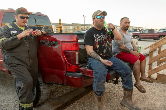 Daniel, Vince, and another oil worker, who declined to give his name, share beers at a man camp in Carlsbad.